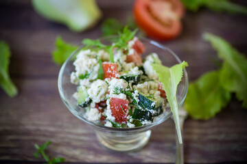 fresh cottage cheese salad with cucumbers and tomatoes with herbs in a bowl