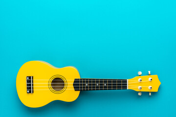 Overhead photo of ukulele with copy space. Yellow colored wooden ukulele guitar on the turquoise blue background.