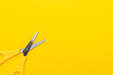 Children's scissors on the yellow background with copy space. Minimalist overhead photo of yellow scissors.
