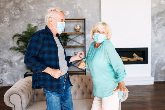 Joyful senior couple with a medical mask on their faces has fun together at home during pandemic, quarantine. A mature man and senior woman wearing protective masks dancing in the living room