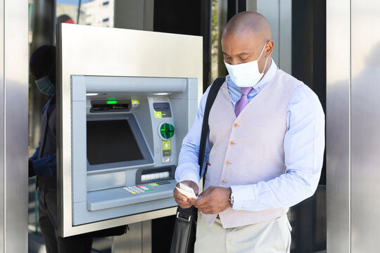 African American entrepreneur withdrawing cash at an ATM. He is wearing a medical mask as a protective measure during the Covid-19 pandemic.