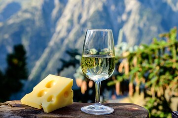 Glass of swiss or savoy dry white wine and yellow emmental cheese with Alpine mountains peaks on...