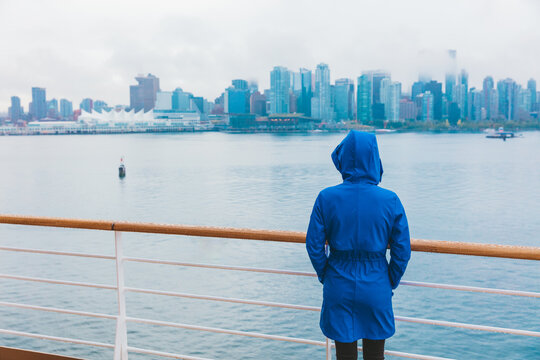 Autumn city scenery woman walking alone under the rain wearing blue raincoat in wet cold day. Skyline of Vancouver, Canada. Cruise ship travel destination.