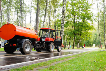 cleaning the park, a small tractor watering the sidewalk