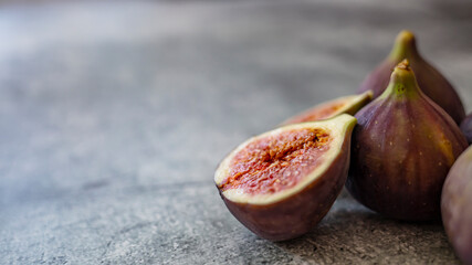 Fresh figs. Food Photo. whole and sliced figs on beautiful rustic background. Fresh Organic Figs.  Healthy Mediterranean fig fruit. Beautiful blue-violet figs with empty copy space close up.