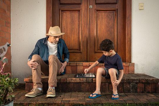 Garoto joga de xadrez com seu avô na escada de casa.