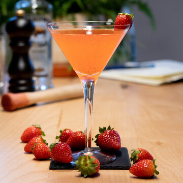 Strawberry Cocktail in martini glass with strawberry in garnish on wood table with muddler and pepper grinder