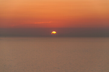 Sun disappearing behind the clouds as it sets over the sea in Zakynthos island, Greece
