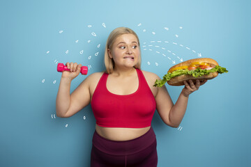 Fat woman does gym and want to eat a sandwich. Concept of food temptation