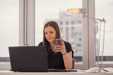 one young woman, holding her smart-phone while using laptop.