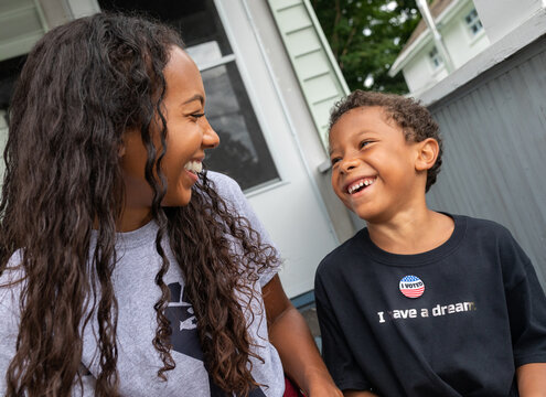 Young African AMerican boy wearing an Ivoted sticker laughing with his multi-racial mother