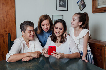 Mexican Sisters using a phone with mother and grandmother through tablet computer