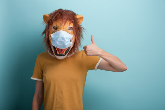 Young woman wearing lion and protection medical mask show thumbs up approval gesture, isolated on blue background.