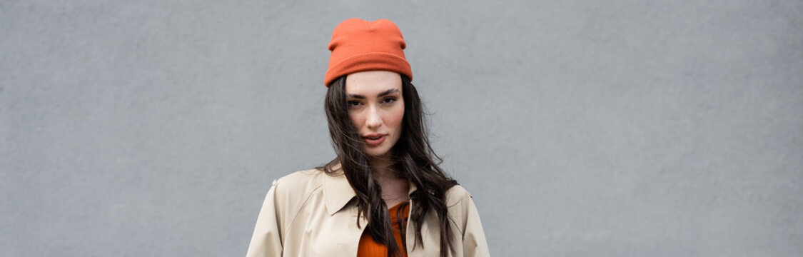 website header of stylish woman in trench coat and beanie hat