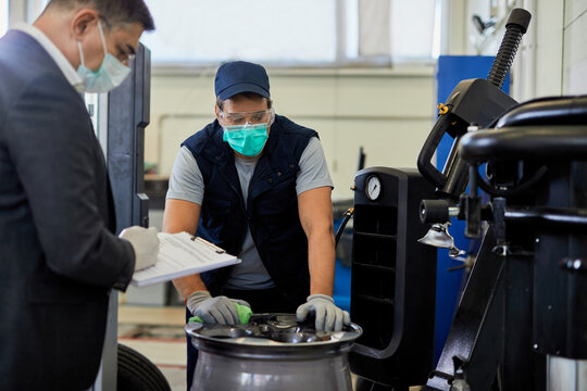 Auto mechanic and his manager wearing protective masks while working in auto repair shop.