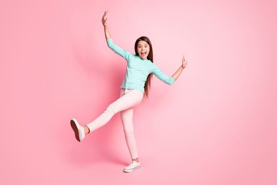 Full body size photo of cute lovely little latin lady long hairdo dance retro disco raise hands up legs wear turquoise sweatshirt pants white sneakers isolated pink color background