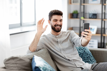 technology, people and lifestyle concept - happy man with smartphone having video call at home