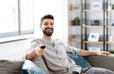 people and leisure concept - happy smiling man with remote control watching tv at home