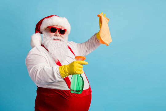 Profile side view portrait of his he nice attractive cheery Santa cleansing wiping using domestic equipment tidy neat fast easy service isolated bright vivid shine vibrant blue color background