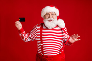 Portrait of his he handsome cheerful bearded Santa holding in hand card order use money transfer service shopping buy pulling suspenders isolated bright vivid shine vibrant red color background