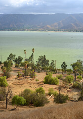 View over Lake Elsinore in California with ancient house structures burned from wildfire