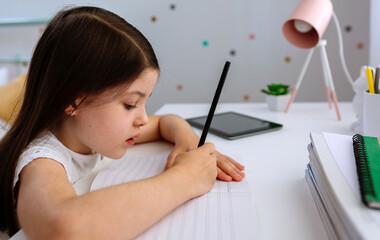 Girl doing homework sitting at a desk in her bedroom