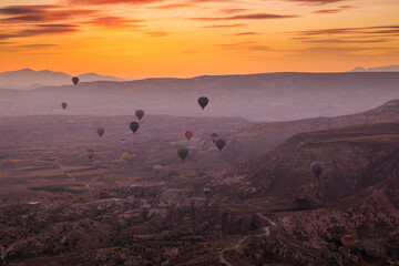 Hot air balloons flying over a volcanic landscape at Cappadocia, Turkey.
