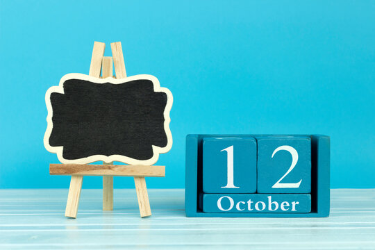 wooden calendar with the date of October 12 and an easel on a blue background, place for text, World Economist Day; World Day of Migratory Birds; World arthritis day