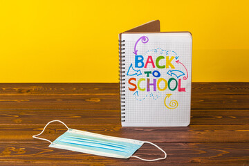Back to school concept with notepad and medical face mask