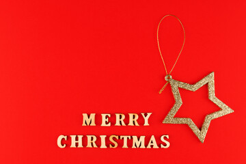 Festive greeting card. Merry christmas lettering on red background with golden glittering star.