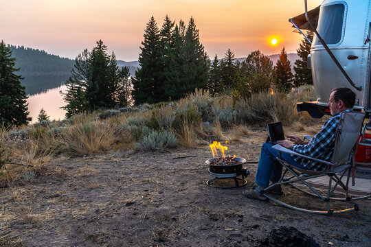 Person sitting on a rocking chair by the side of a travel trailer, RV, campfire working on a laptop, PC as the sun setting over a distance hill, mountain, Half Moon Lake, Pinedale, Wyoming