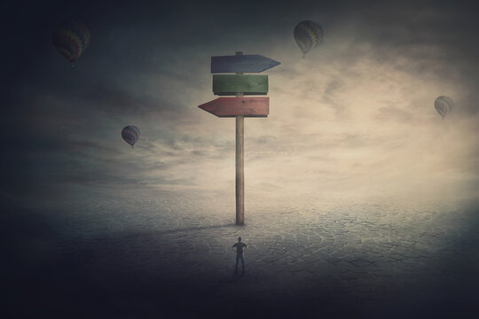 Surreal scene, tiny man stands in front of a huge signpost with three different directions. Choosing the correct way to unknown future. Courses to left and right side. Road splits, choice concept.