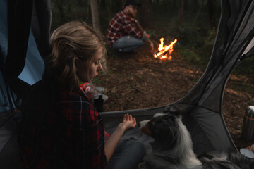 Woman and Aussie Dog In Tent, Bearded Hipster Man Near Bonfire Out Of The Tent In Dark Autumnal Forest. Travelling With Closed Borders