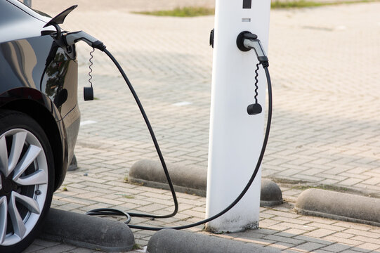 Electric car connected to charge station for charging the battery