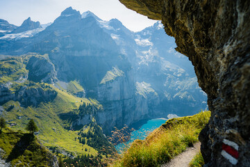 Photo sur Plexiglas Bleu jean Idyllic panorama view of the lake Oeschinensee travel destination. Man tourist alone, looking at landscape of Swiss Alps. Discover the beauty of earth.