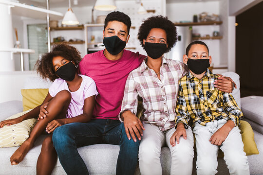 African American parents and cute small kids wearing protective masks at home. Stop the virus and epidemic diseases.