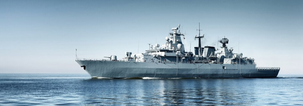 Large grey modern warship sailing in still water. Clear blue sky. Baltic sea, Germany. Global communications, international security theme. Panoramic image, copy space