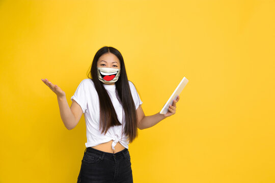 Smiling. Portrait of young girl with emotion on her protective face mask on studio background. Beautiful female model, funny expression. Human emotions, facial expression, sales, ad, healthcare