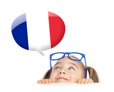 beautiful cute little girl hiding under table and curiously looking at the France flag speech ballon above her head