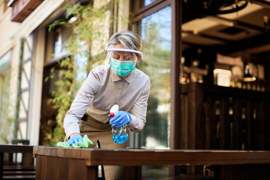 Waitress disinfecting tables while reopening cafe after COVID-19 quarantine.