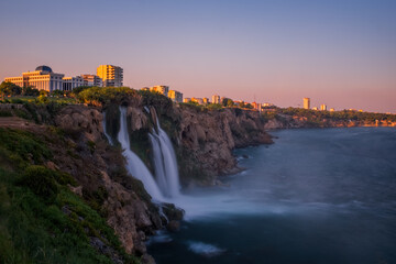 Duden lower waterfalls cascade at sunset in the sea at Antalya, Turkey. July 2020, long exposure picture