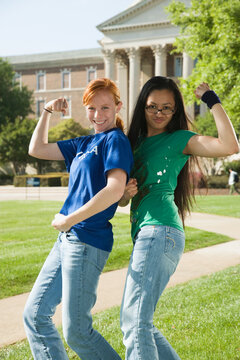 Friends flexing biceps on college campus