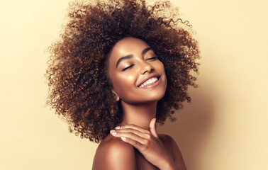 Beautiful black woman . Beauty portrait of african american woman with clean healthy skin on beige background.  Smiling beautiful afro girl.Curly black hair Wall mural