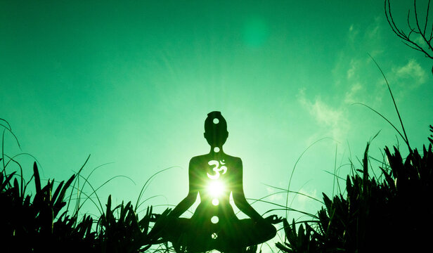 yoga position silhouette in contrasting sun, Heart chakra