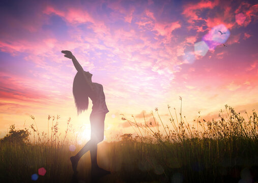 Celebration of life day concept: Silhouette of healthy woman raised hands for praise and worship God at autumn sunset meadow background