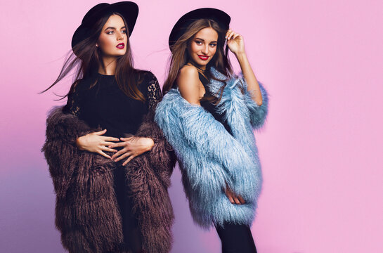 Positive fashion portrait of two girls, best friends posing indoor on bright pink background wearing winter stylish fluffy coat, black casual hat. Fashionable clothes.  Sisters walking.