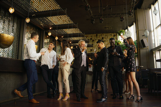 corporate businesspeople having fun and talking together in party