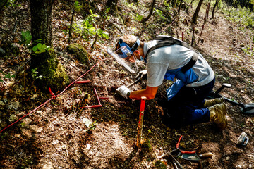 Deminer excavating a landmine in a minefield