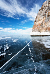 Baikal Lake in February. View of the Three Brothers cliffs on Olkhon Island from smooth blue ice. Winter travel on the endless ice surface. Natural background