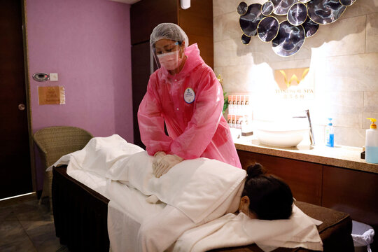 An employee wearing a protective suit practice massaging on a model customer at a Sauna & Spa centre to prepare reopen, following the coronavirus disease (COVID-19) outbreak, in Hong Kong